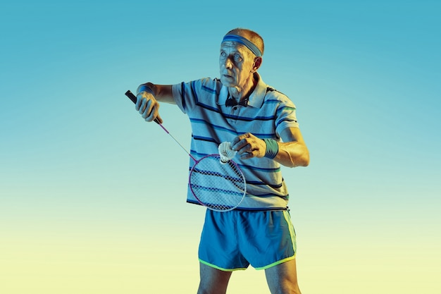 Senior man wearing sportwear playing badminton on gradient background, neon light. caucasian male model in great shape stays active. concept of sport, activity, movement, wellbeing, confidence.