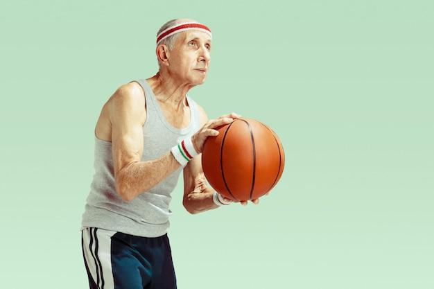 Senior uomo che indossa abbigliamento sportivo giocando a basket sul verde