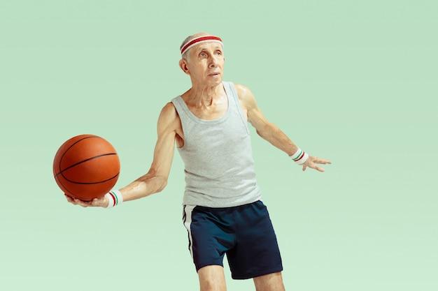 Старший мужчина в спортивной одежде играет в баскетбол на зеленом