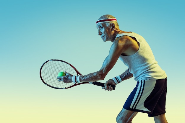 Senior man wearing sportwear playing tennis on gradient background, neon light. caucasian male model in great shape stays active, sportive. concept of sport, activity, movement, wellbeing, confidence.