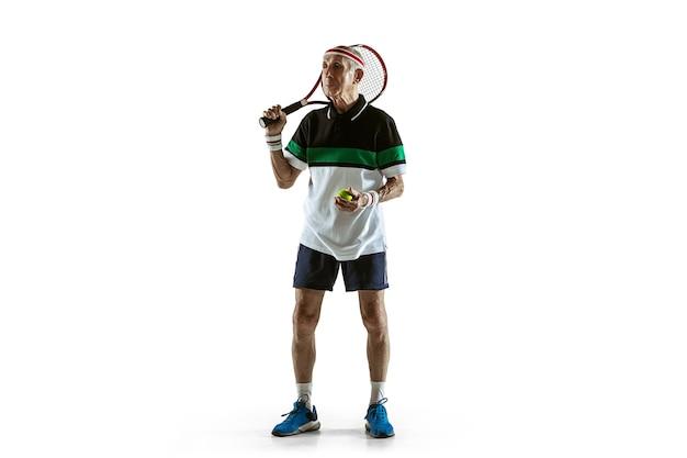 Старший мужчина в спортивной одежде, играя в теннис, изолированные на белом фоне. кавказский мужчина-модель в отличной форме остается активным и спортивным. понятие спорта, активности, движения, благополучия. copyspace, объявление.