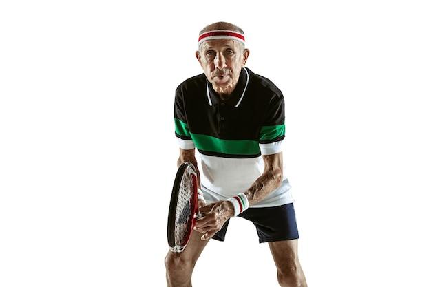 Старший мужчина в спортивной одежде, играя в теннис, изолированные на белой стене. кавказский мужчина-модель в отличной форме остается активным и спортивным. понятие спорта, активности, движения, благополучия. copyspace, объявление.