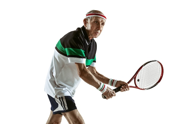 Senior man wearing sportwear playing tennis isolated on white wall. caucasian male model in great shape stays active and sportive. concept of sport, activity, movement, wellbeing. copyspace, ad.