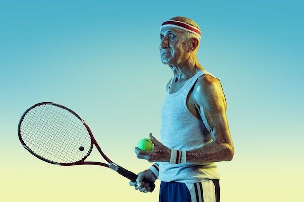 Старший мужчина в спортивной одежде, играя в теннис на градиентном фоне, неоновый свет. кавказский мужчина-модель в отличной форме остается активным, спортивным. понятие спорта, активности, движения, благополучия, уверенности.