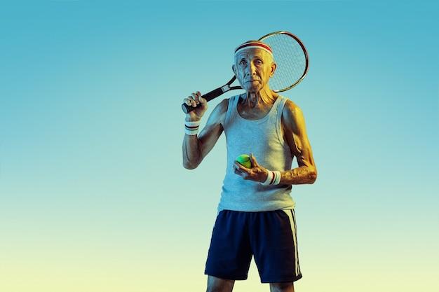 勾配でテニスをしているスポーツウェアを着ている年配の男性