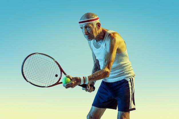 Старший мужчина в спортивной одежде играет в теннис на градиенте