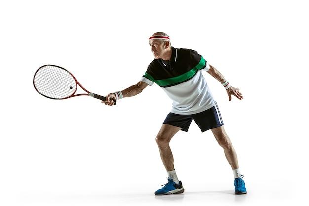 Старший мужчина в спортивной одежде, играя в теннис на белом