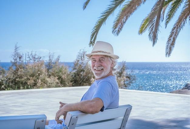 Senior man wearing straw cap sitting outdoor at sea looking at camera smiling - horizon over water