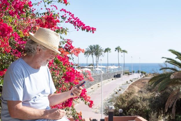 Senior man wearing straw cap sitting outdoor at sea using mobile phone. horizon over water