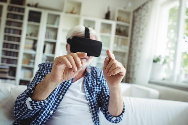 リビングルームで仮想現実のヘッドセットを着ている年配の男性