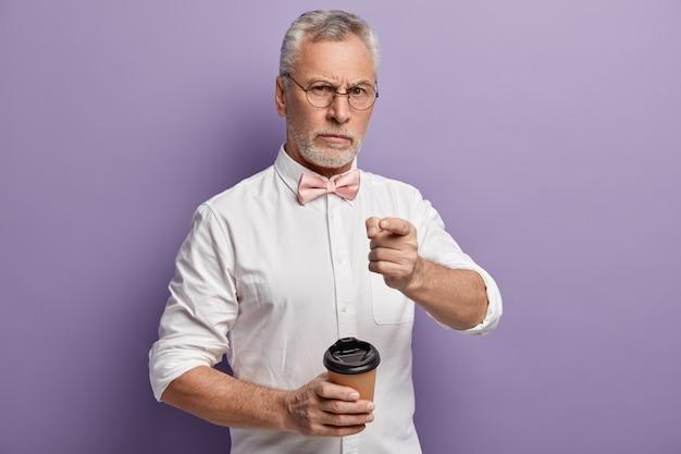 Старший мужчина в белой рубашке и розовом галстуке-бабочке