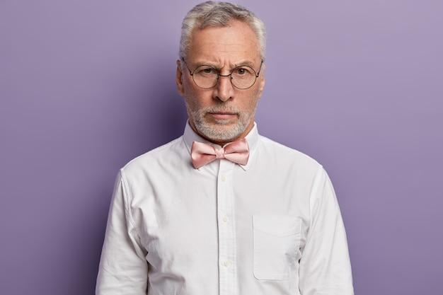 Uomo maggiore che indossa una camicia bianca e papillon rosa