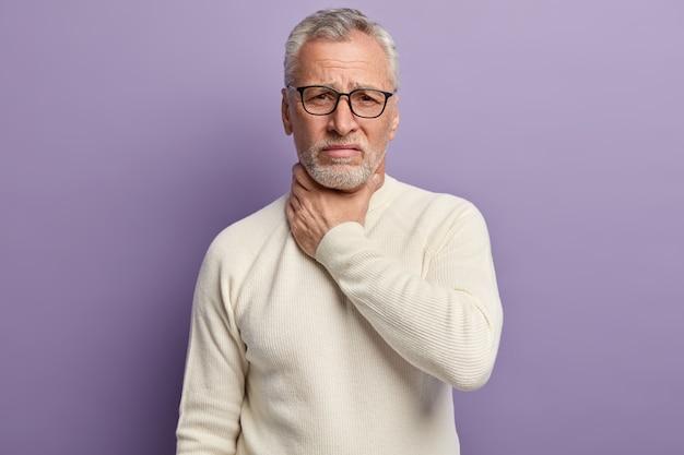 Старший мужчина в белом свитере и модных очках