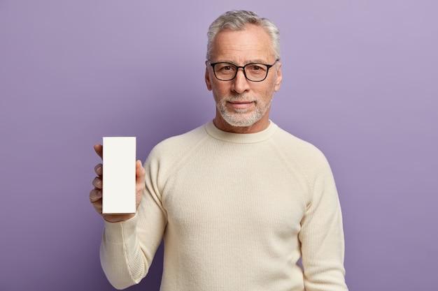 Senior uomo che indossa un maglione bianco e tenendo il telefono