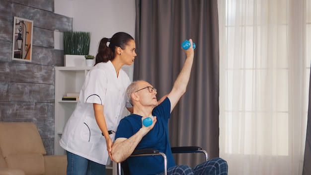 Senior man in wheelchair doing professional injury recovery. disabled handicapped old person with social worker in recovery support therapy physiotherapy healthcare system nursing retirement home