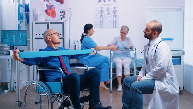 Senior man in wheelchair exercising muscle strength with elastic band under medical supervision in modern recovery clinic or hospital. invalid physiotherapy program, health care injury rehabilitation