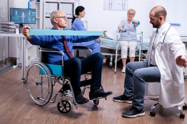 Uomo anziano in sedia a rotelle che esercita la forza muscolare