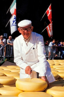 Senior man in white coat and cap cutting large wheel of cheese at outdoor festival