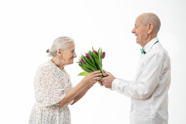 Senior man in white shirt gives flowers to elderly woman