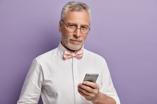 Senior man in white shirt and pink bowtie holding phone
