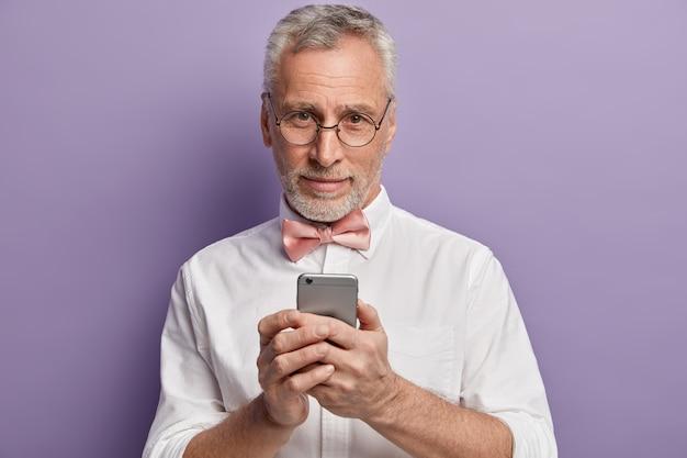 Uomo maggiore in camicia bianca e papillon rosa che tiene telefono
