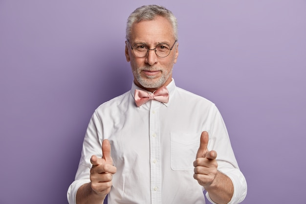Senior man in white shirt and pink bowtie