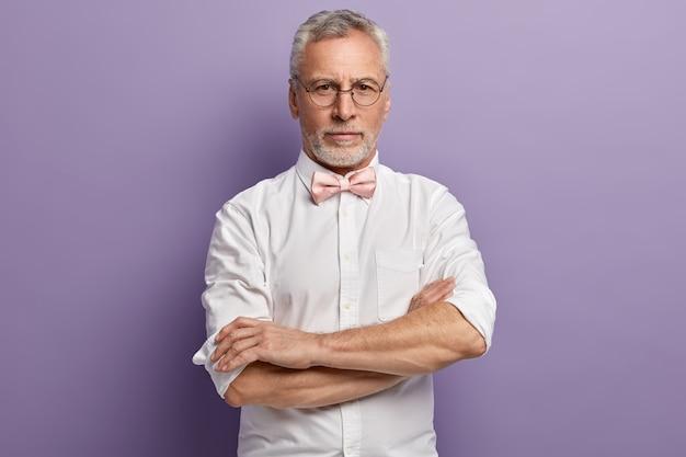 Uomo anziano in camicia bianca e papillon rosa