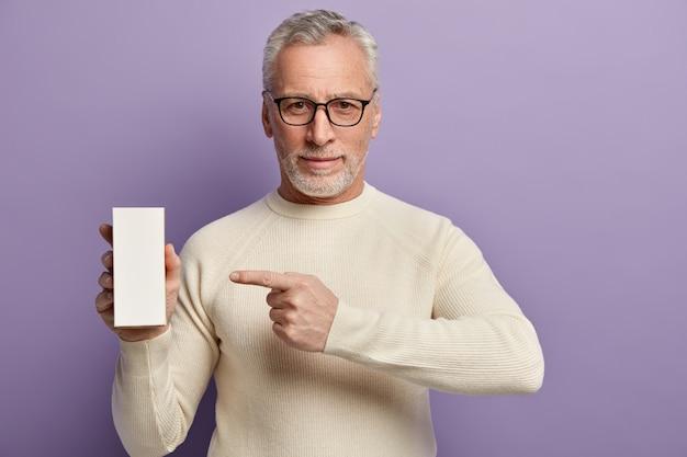 Uomo maggiore in maglione bianco e occhiali da vista