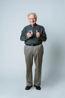 물 한 잔을 가진 시니어 남자