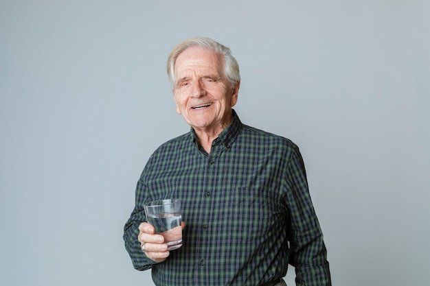 Старший мужчина со стаканом воды