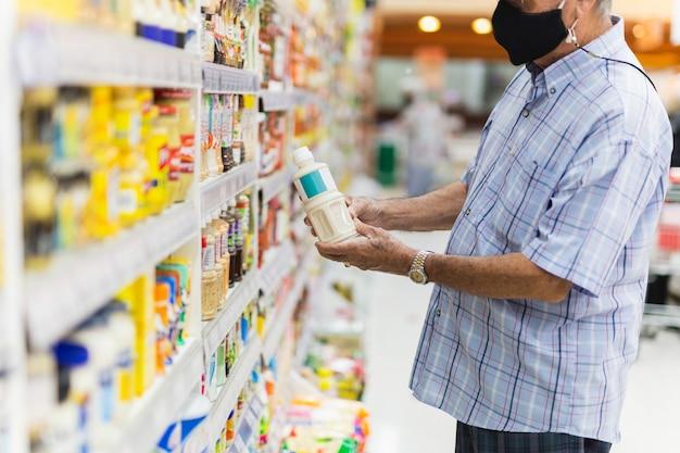 スーパーマーケットで保護マスクを持つ年配の男性