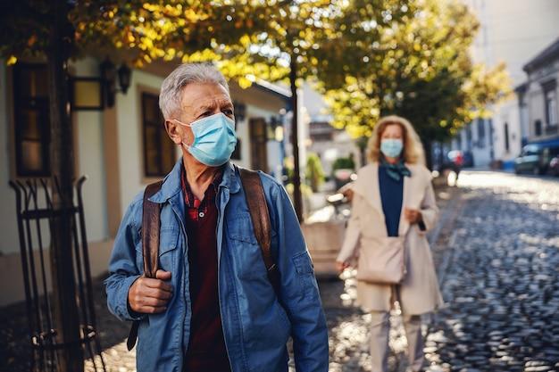 Старший мужчина с защитной маской на прогулке по центру города. на заднем плане - старшая женщина в маске