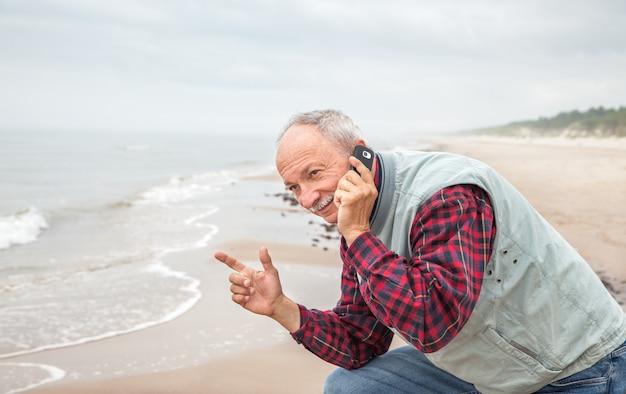 海の背景に電話で年配の男性