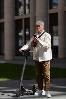 Старший мужчина с электросамокатом в городе с помощью смартфона и наушников