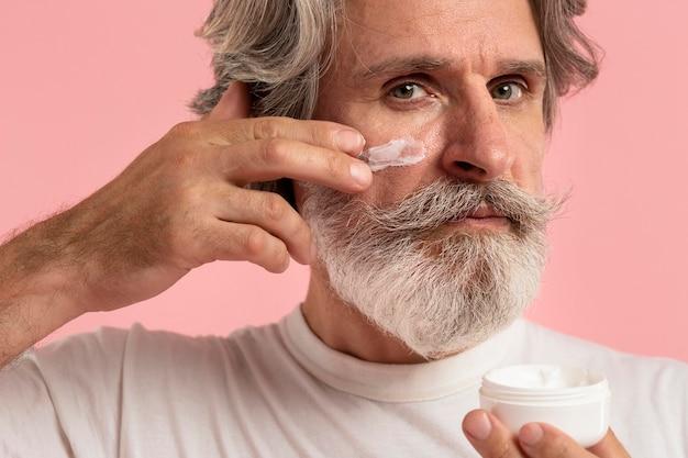 Uomo senior con la barba che applica crema