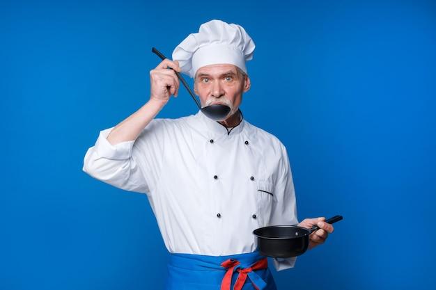 Старший мужчина с бородой повар с возбужденным лицом в форме с ковшом