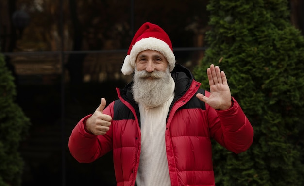 屋外何かを提示する赤いサンタ帽子のひげを持つシニア男。クリスマス。新年。