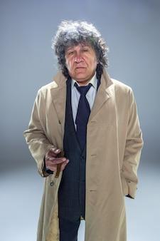 L'uomo senior con il sigaro come agente investigativo o capo della mafia sul fondo grigio dello studio