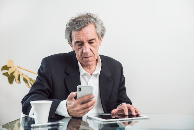 Senior man with digital tablet looking at mobile phone