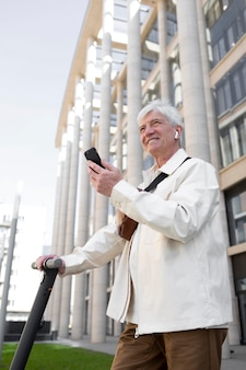 Senior man with an electric scooter in the city using smartphone and earbuds