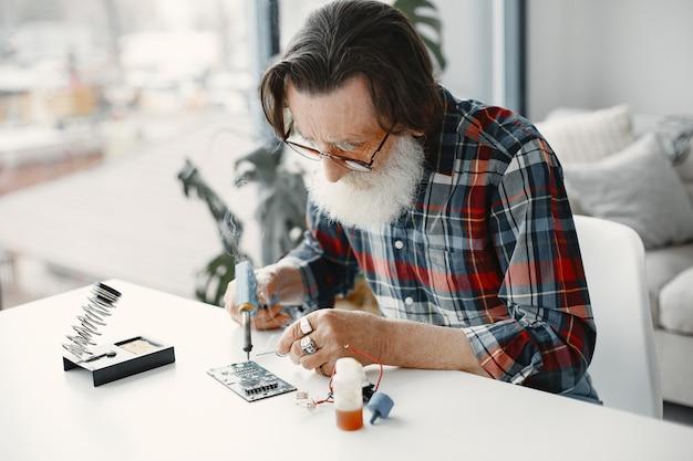 はんだ付け装置を持った年配の男性。在宅勤務。