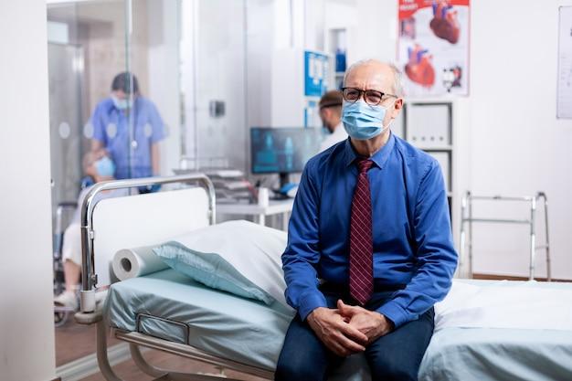 Старший мужчина с маской для лица против covid ждет консультации врача в больничном кабинете