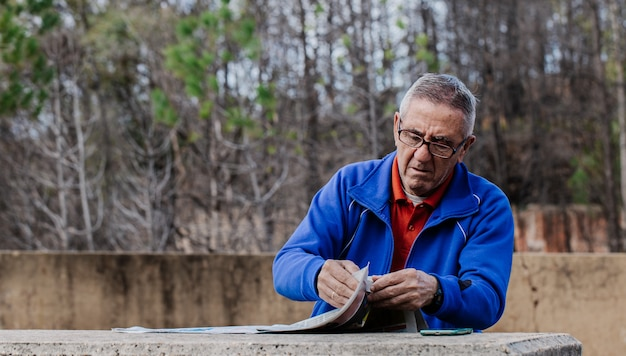 Senior man with glasses reading newspaper at park