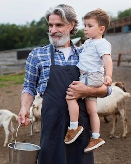 Uomo anziano con il nipote in fattoria