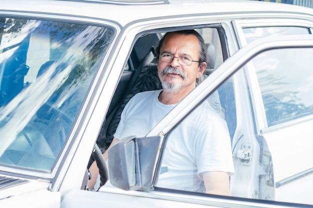 Senior man with gray mustache wearing glasses and white t-shirt sits in white car with open door and smiles
