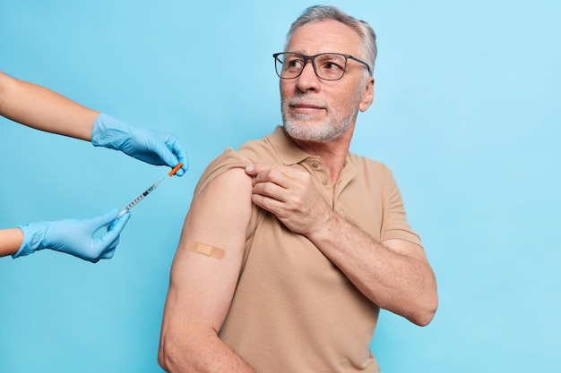 Senior man with grey beard engaged in free vaccination program gets vaccine in arm listens attentively nurse advice wears spectacles beige t shirt poses against blue wall