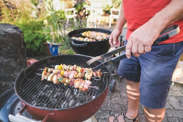 グリルトングを持った年配の男性がグリルで肉と野菜の串焼きを回す-庭でのバーベキューパーティー