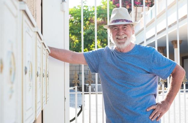 Старший мужчина в шляпе улыбается, стоя рядом с белыми почтовыми ящиками, висящими на стене.