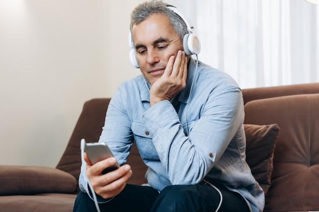 헤드폰을 끼고 있는 노인이 휴대전화로 재미있는 영화를 보고 있습니다. 잠금 기간 동안의 엔터테인먼트. 성숙한 남자는 인터넷에서 비디오를 보고 긴장을 풀고 있습니다. 배경에 거실입니다.
