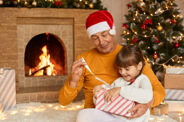 Senior man with his granddaughter sitting on floor and opening present box, old male in yellow shirt and red festive hat helps to little girl to see her present, posing with xmas tree